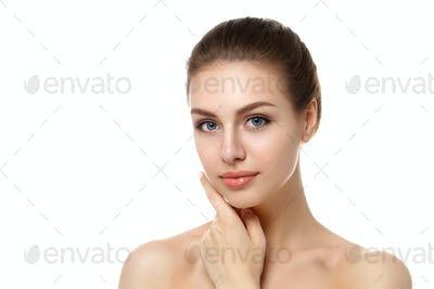 Portrait of young woman touching her face