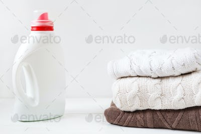 White bottle with liquid detergent and laundered flesh colored soft pullovers.
