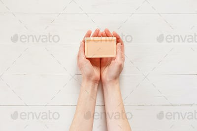 Top view of woman hands with solid soap on white wooden background.