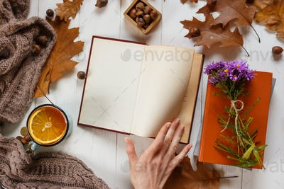 education and people concept - hands of woman reading book at wooden table