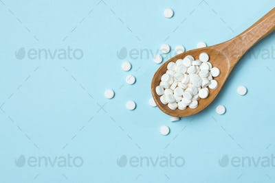 White pills on wood spoon