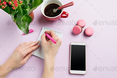 The female hands holding pen. The phone and french macarons on trendy pink desk.