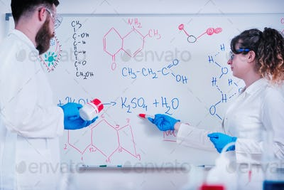 Young Scientist Standing In Front Of Board In Laboratory