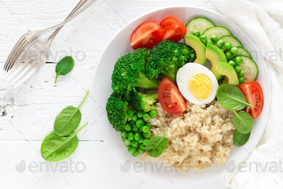 Healthy detox dish with egg, avocado, quinoa, spinach, fresh tomato, green peas and broccoli