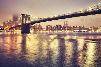 Brooklyn Bridge on a foggy night, New York, USA.