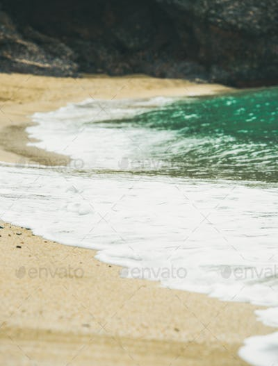 Blue sea water and sandy beach with rock at background, selective focus