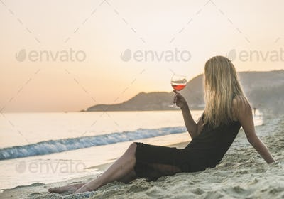 Young woman enjoying glass of rose wine on beach