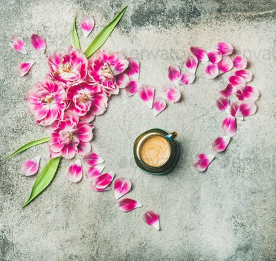 Cup of coffee, pink tulip flowers and petals