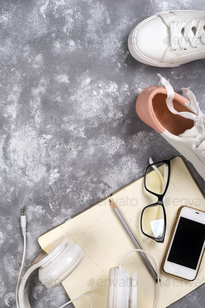 Summer holiday concept: smartphone , white sneakers, notepad, headphones, pen