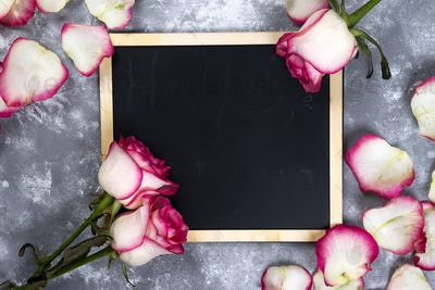 Beautiful rose flowers on gray stone table. Floral border.