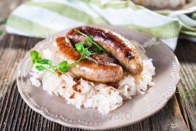Plate of sausages and sauerkraut on wooden table