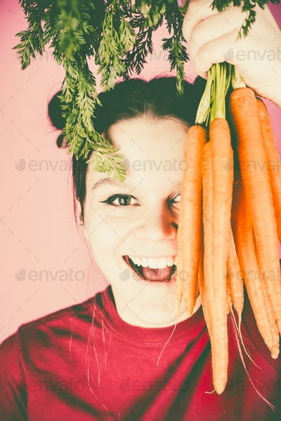 Teenage girl holding bunch of fresh carrots over pink background
