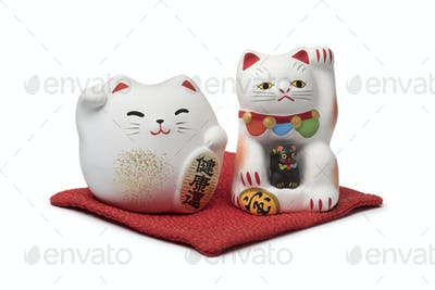 Japanese maneki neko, lucky cats on a red pillow