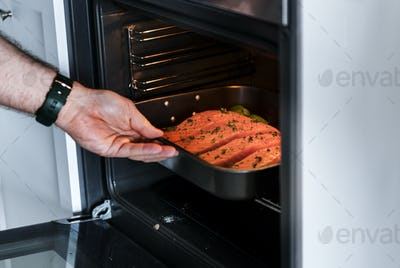 Man putting raw salmon steak into oven