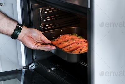 Man putting raw salmon steak into oven