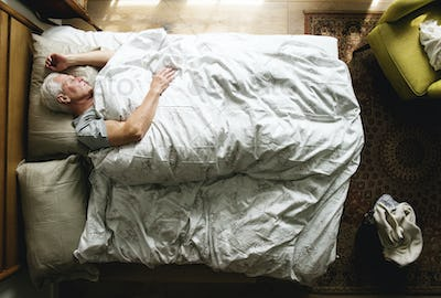 Elderly Caucasian man sleeping on the bed