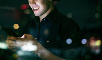 Happy young adult male using a smartphone in a night cityscape