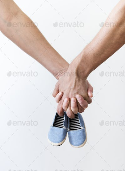 Couple hands holding baby boy girl shoes