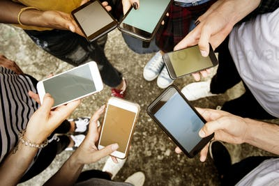 Young adults using smartphones in a circle social media and conn