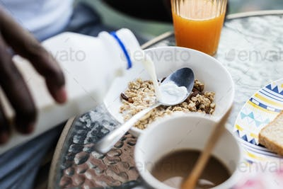 Closeup of hand pouring milk into cereal
