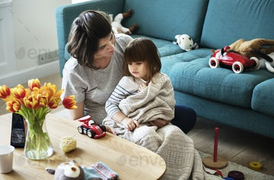 Pregnant woman and daughter playing in a living room together