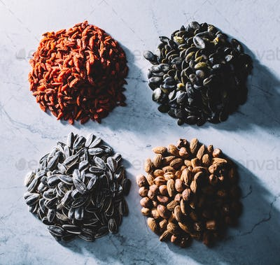 Four piles of superfoods on light background.