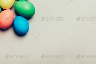 Four colored eggs in a corner on creamy background