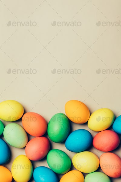 Bunch of dyed eggs laying on the floor.