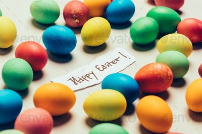 """""""Happy Easter"""" writing and bunch of colorful dyed eggs."""