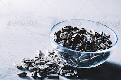Little black sunflower seeds in a glass bowl.
