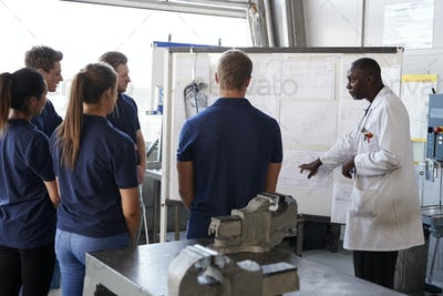 Engineer instructing apprentices at a whiteboard, close up