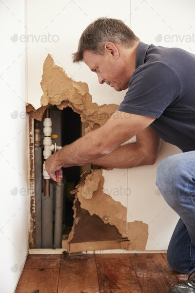 Middle aged man repairing burst water pipe, vertical