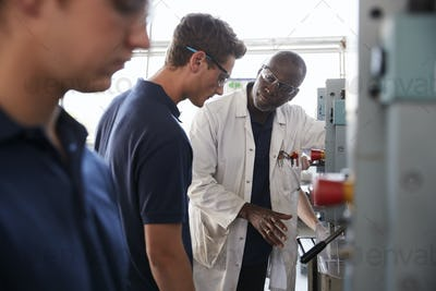 Engineer instructing male apprentice at a drill press