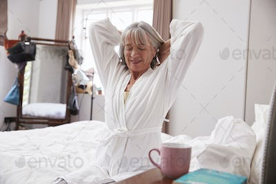 Senior Woman Waking Up And Stretching In Bedroom