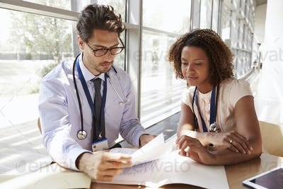 Male and female senior doctors reading patient notes