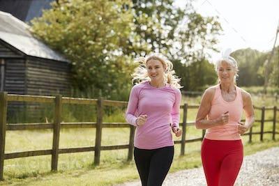 Young And Senior Women Enjoying Run Through Countryside Together