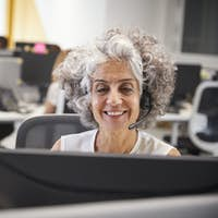 Middle aged woman working at computer with headset in office