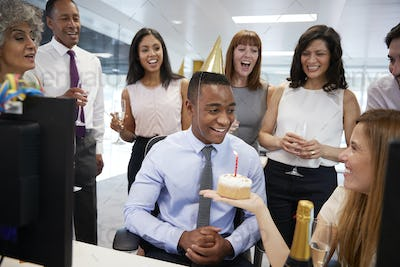 Colleagues gathered at a man's desk to celebrate a birthday