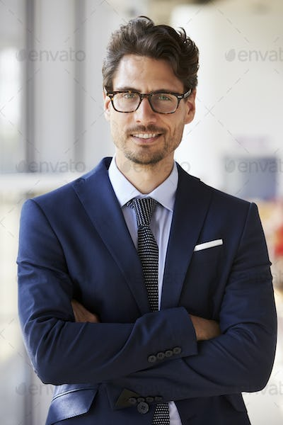 Portrait of young professional man in suit, arms crossed