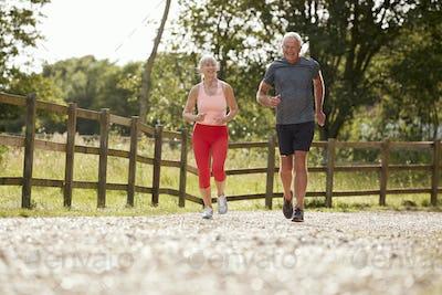 Healthy Senior Couple Enjoying Run Through Countryside Together