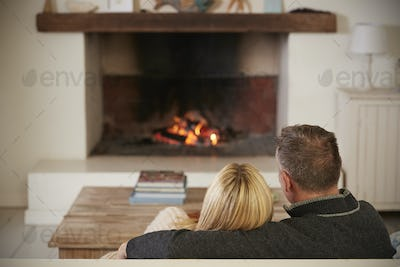 Romantic Couple Relaxing In Lounge Next To Open Fire
