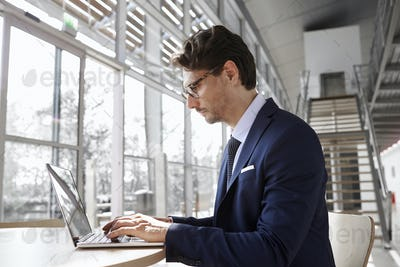 Young professional man using laptop, close up