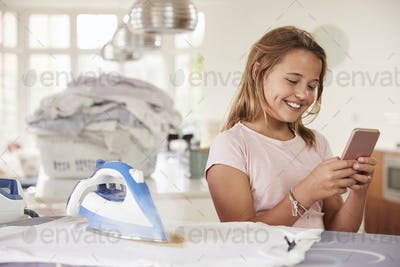 Young girl using distracted by phone while ironing