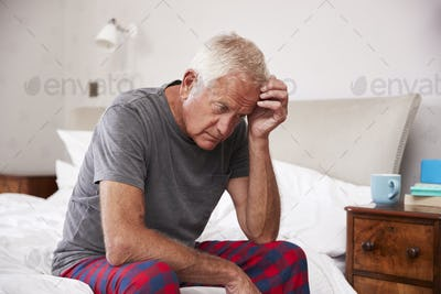 Senior Man Sitting On Bed At Home Suffering From Depression