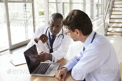 Two senior healthcare workers in consultation using laptop