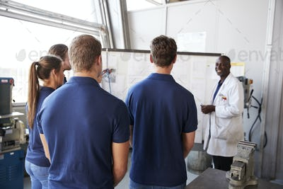 Engineer instructing apprentices at white board, back view
