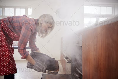 Middle aged woman opening smoke filled oven in the kitchen
