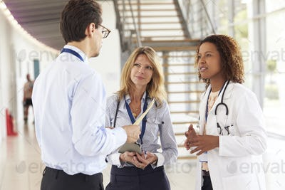 Three young male and female doctors in consultation