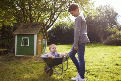 Boy Pushing Baby Brother In Garden Wheelbarrow