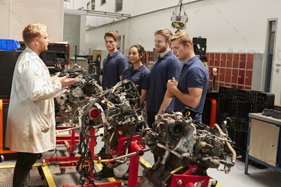 Apprentices studying car engines with a mechanic